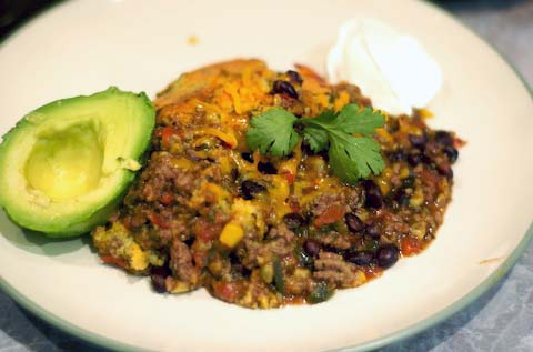 Serving of tamale pie w/avocado and sour cream