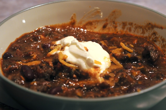 Bowl of Chili, topped with cheddar and sour cream