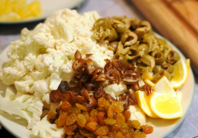 Coarsely dice up cauliflower, green olives, dates, and raisins