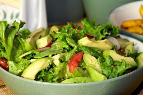 Simple salad of lettuce, tomato, radish, olive, avocado, and lime